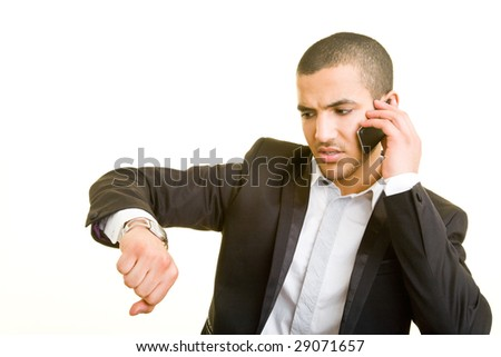 Young business man on the phone looking at his watch - stock photo