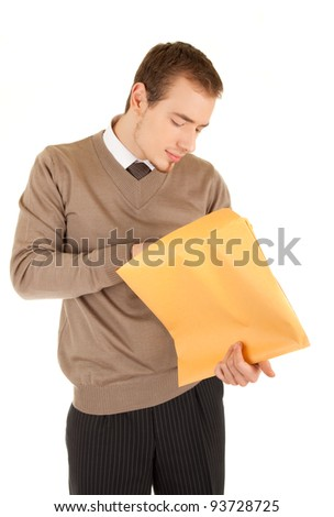 Young business man opens a yellow post package with interest. Isolated on white.