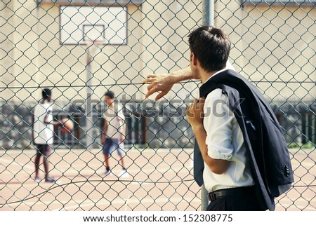 Young Business man or father looking two boys playing basketball  - stock photo