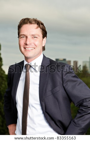 Young business man outdoors on top of building with cloudy sky. - stock photo