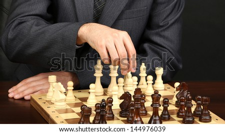 Young business man playing chess on black background - stock photo
