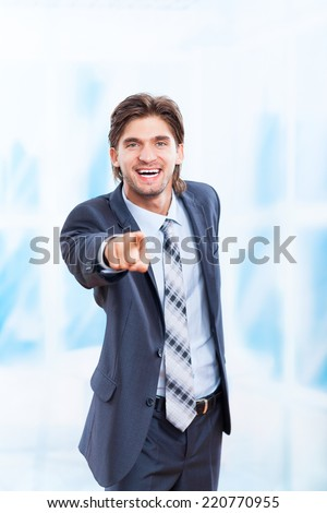 young business man point finger at you happy smile in bright blue office, Handsome businessman wear elegant suit and tie - stock photo