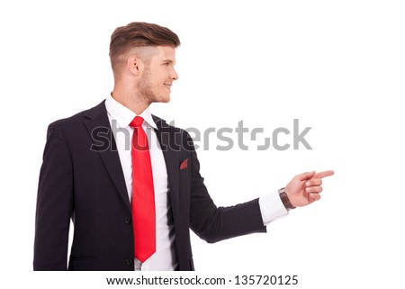 young business man pointing and looking to his side with a smile on his face. isolated on white background