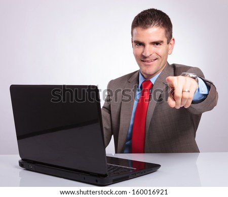 young business man pointing at the camera while smiling from behind his laptop. on a gray background