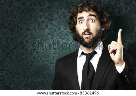 young business man pointing up against a grunge background - stock photo