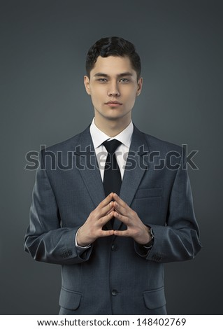 Young business man portrait in gray background