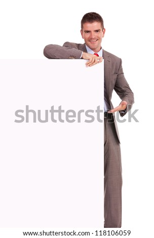 Young business man presenting something on a blank board on white background