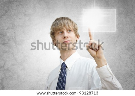 Young business man pressing a button on a touch screen - stock photo