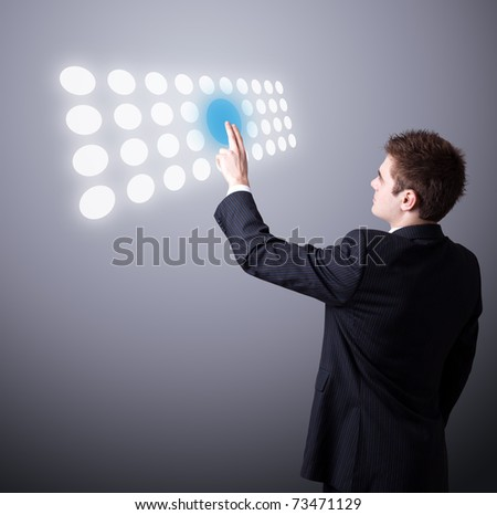 Young business man pressing a touchscreen button - stock photo