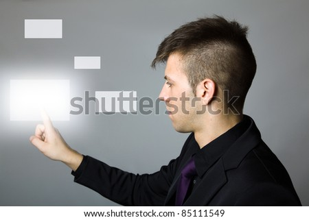 Young business man pressing a touchscreen button