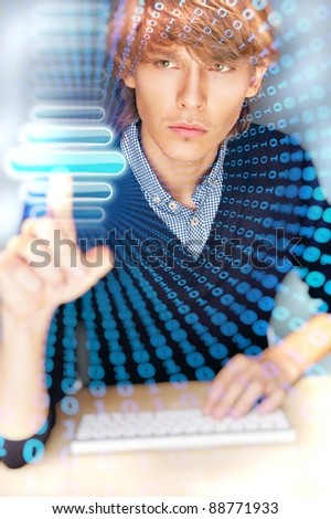 Young business man pressing a touchscreen button while working at his modern office - stock photo
