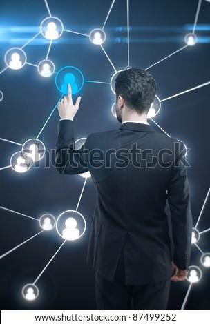 Young business man pressing a touchscreen Social Network button - stock photo