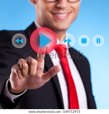 young business man pushing a play button on a virtual screen - stock photo