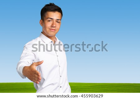 young business man putting his hand out - stock photo