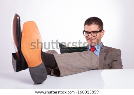 young business man reading a book while holding his feet on his desk, with a smile on his face. on a gray background - stock photo