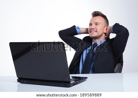 young business man relaxing at the laptop with his hands behind his head and looking away with a smile on his face. on a gray studio backgroud