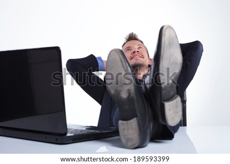 young business man relaxing with his feet on the desk, near his laptop, while holding his hands behind his head and looking up with a smile on his face. on a gray studio background