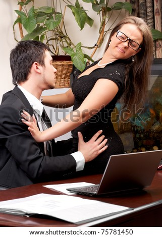 Young business man sexually harassing woman in office - stock photo