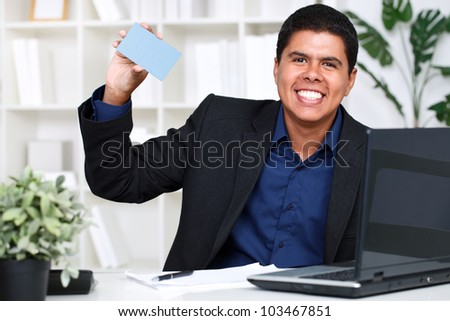 young business man showing a business card in office - stock photo