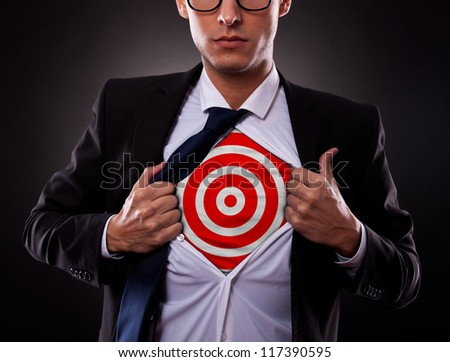 Young business man showing a target under his shirt on dark background - stock photo