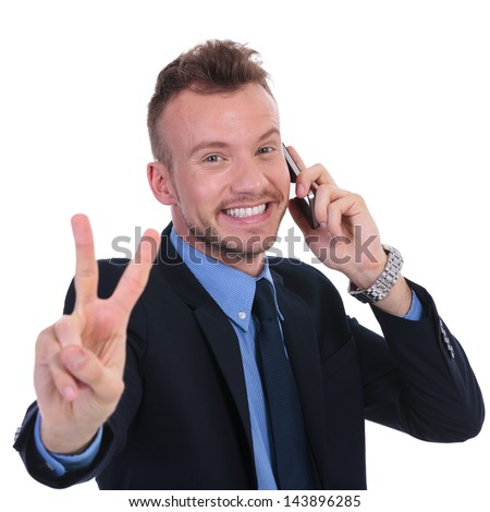 young business man showing victory sign while on the phone. on white background