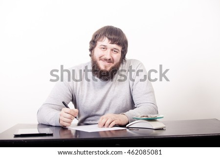 Young business man signs contract sitting at the desk in office.