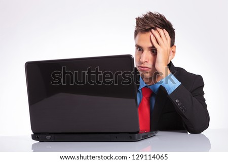 young business man sitting at desk is overwhelmed of too much work on his laptop - stock photo