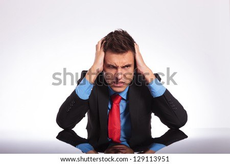 young business man sitting at his desk and looking despaired away from the camera with a mad look on his face - stock photo