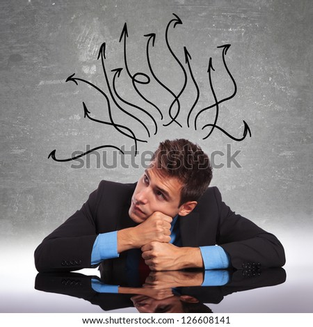 young business man sitting at his desk with his mind in all directions