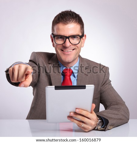 young business man sitting at the desk with a tablet in his hand and pointing and smiling at the camera. on a gray background