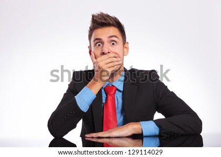 young business man sitting at the office and looking shocked at the camera covering his mouth with his hand - stock photo