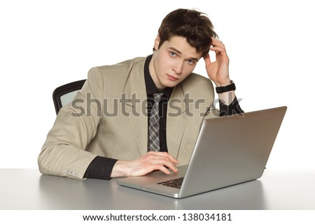 Young business man sitting at the table with laptop, scratching his head, over white background