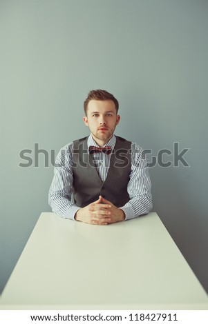 Young business man sitting at the white long table - stock photo