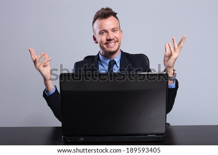 young business man sitting behind his laptop and welcoming you with a smile. on a gray studio background
