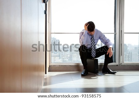 Young business man sitting in depression with hand on head - stock photo