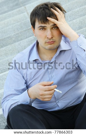 Young business man sitting on the stairs of the building smoking a cigarette
