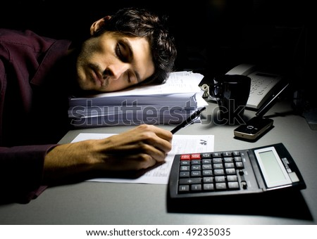 Young business man sleeping on a pile of documents - stock photo
