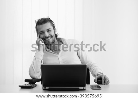 young business man smiling, office, work, black and white - stock photo