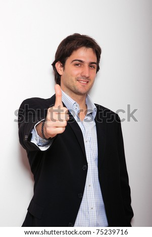 Young business man standing against the wall thumb up