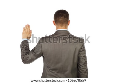 Young business man standing and making an oath with his back toward us - stock photo