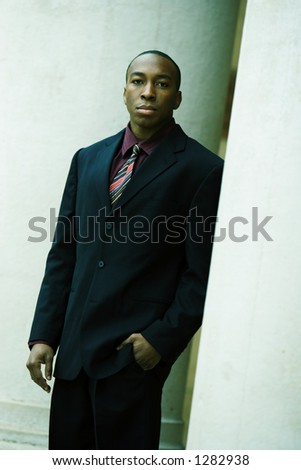 young business man standing between pillars - stock photo