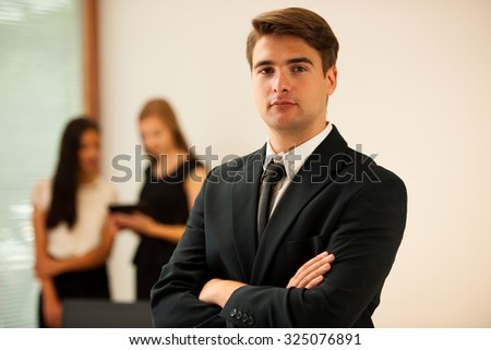 Young Business man   standing in first plain with coworkers in background  Young boss entrepreneur - stock photo
