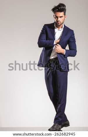 Young business man standing on grey studio background pulling his coat and putting something inside. - stock photo