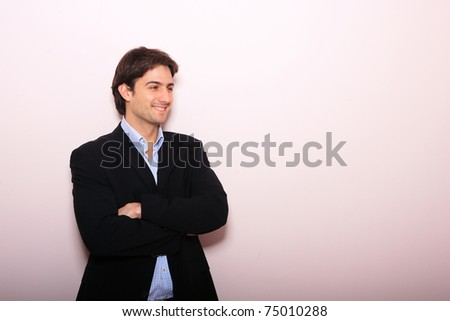 Young business man standing with arms folded over light pink wall - stock photo