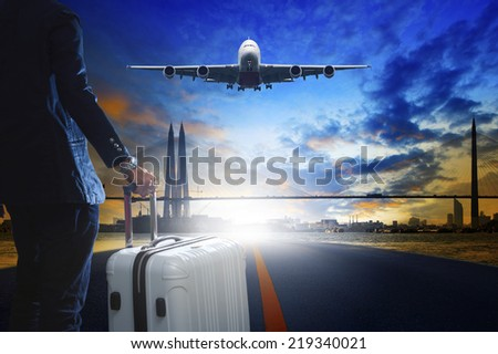 young business man standing with luggage on urban airport runway and jet plane flying above against beautiful urban scene behind