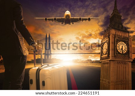 young business man standing with luggage on urban airport runway and jet plane flying above against beautiful urban scene and big ben london behind - stock photo