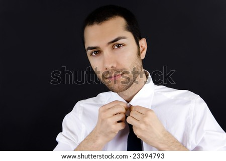 Young business man straightening his tie - stock photo