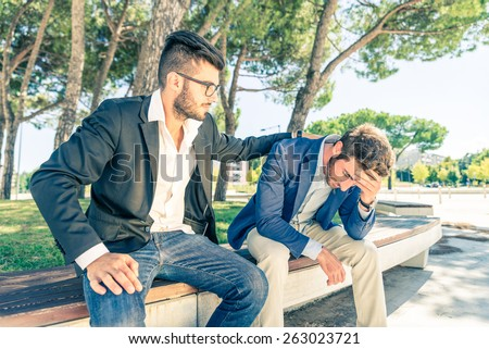 Young business man supporting a depressed person - Man supporting his friend despairing for his financial problems  - stock photo