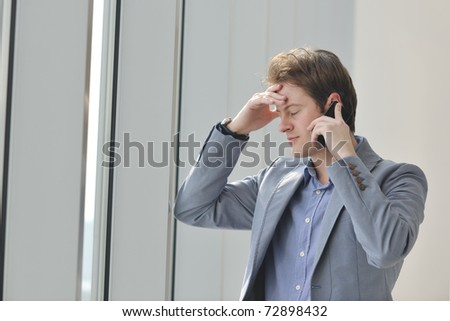young business man talk by cellphone over bright window in big hall - stock photo