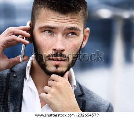 Young business man talking on cell phone near modern office - stock photo